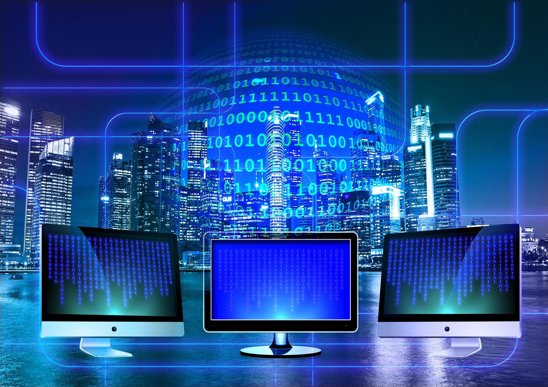 Computer screens against skyscraper backdrop