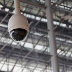 Surveillance camera hanging from the top of a building.