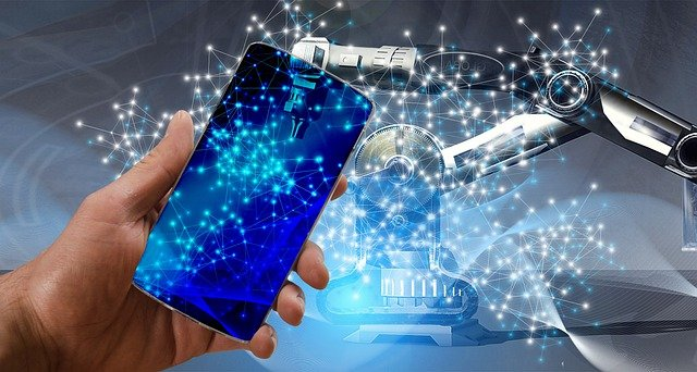 Human hand holding a smartphone. AI machine in the background working on the phone.